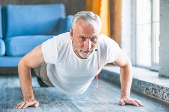 senior-man-doing-pushup-at-home_23-2147859867